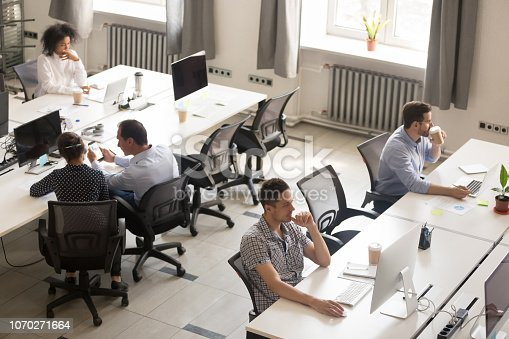 1090214584 istock photo Diverse office workers using computers in modern corporate space 1070271664