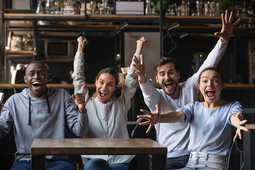 Multi-ethnic people looking at camera sitting at cafe public place screaming shouting feels overjoyed happy by favourite football club team winning get victory, sports betting, lottery winners concept