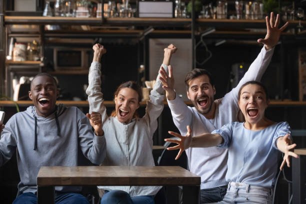 Diverse overjoyed football fans looking at camera screaming feels happy Multi-ethnic people looking at camera sitting at cafe public place screaming shouting feels overjoyed happy by favourite football club team winning get victory, sports betting, lottery winners concept cheering stock pictures, royalty-free photos & images