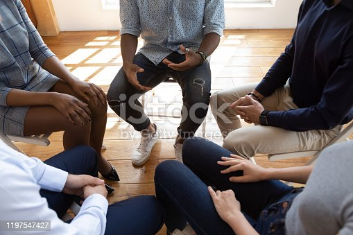 Close up top view unrecognizable multiracial workers strategizing indoors at informal atmosphere, people seated in circle talking share problems tell stories during psychological rehab session concept