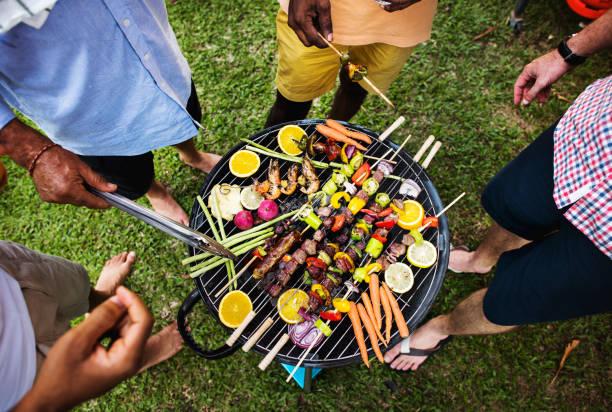 diverse leute grillparty zusammen genießen - grillgemüse stock-fotos und bilder