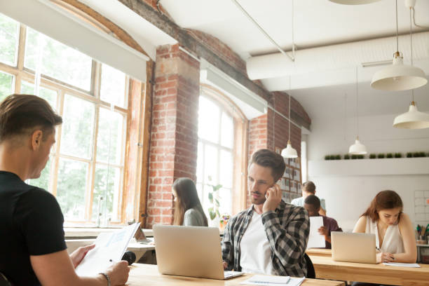 Diverse people focused on work in modern loft co-working space stock photo