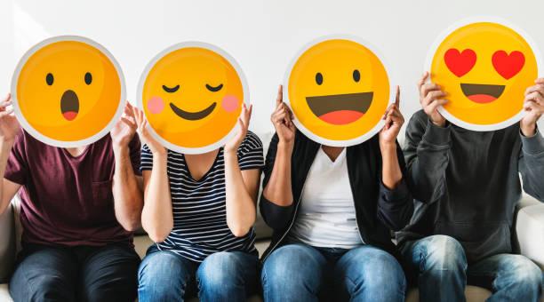 unterschiedlichste menschen halten emoticon - emojis stock-fotos und bilder