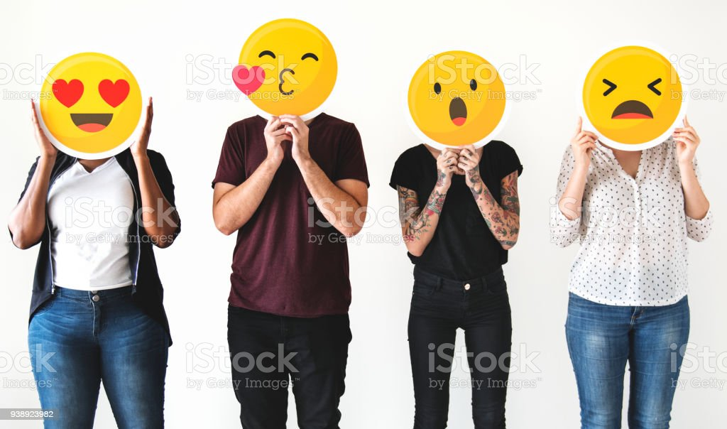 Diverse people holding emoticon stock photo
