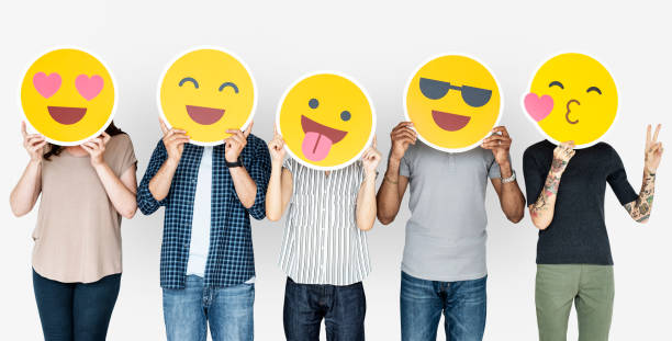 diverse people holding happy emoticons - emoji foto e immagini stock