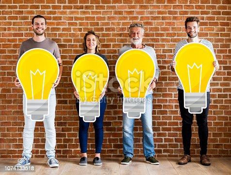 1094812112 istock photo Diverse people holding light bulb icons 1074133518