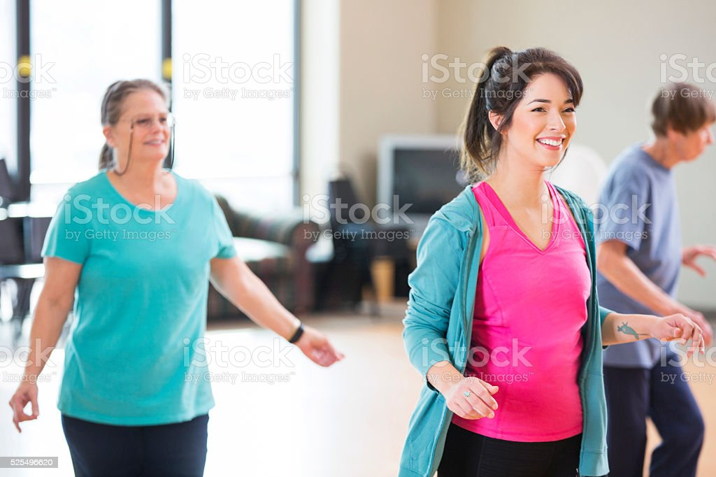 Young female line dancing instructor teaches a group of seniors to...