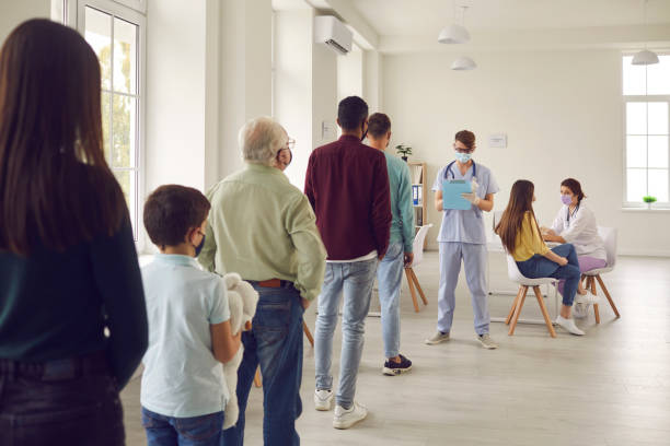 Diverse people lining up waiting for their turn to get shots in modern vaccination center stock photo