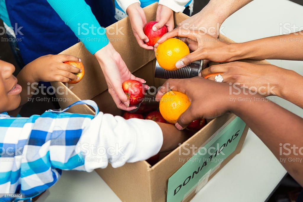 Diverse people placing fruit in box at food drive stock photo