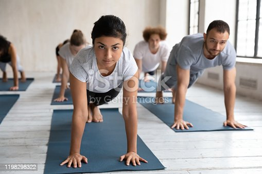 944619806 istock photo Diverse people practicing yoga at group lesson, doing Plank exercise 1198298322
