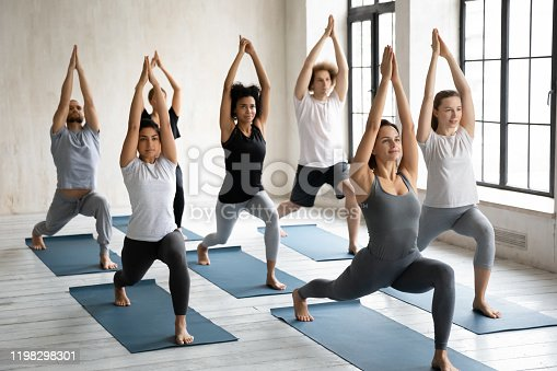 Diverse young people wearing sportswear practicing yoga at group lesson, standing in Warrior one pose, doing Virabhadrasana exercise, working out in modern yoga studio with female instructor