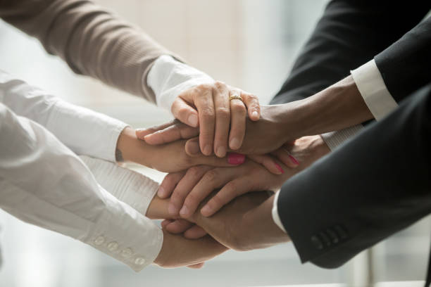 diverse people putting hands together promising help and support, closeup - employee engagement stock photos and pictures