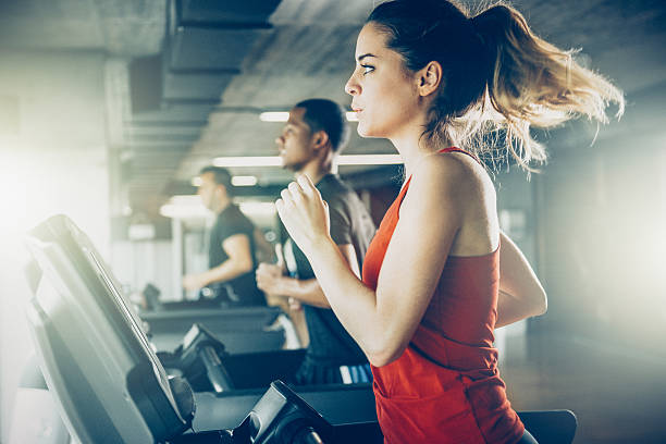 diverse people running on treadmill - health club stock photos and pictures