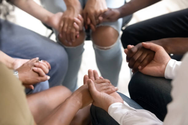 Diverse people sitting in circle holding hands at group therapy Diverse people sitting in circle holding hands at group therapy session, religious christian team pray together for recovery give psychological support, counseling training trust concept, close up religion stock pictures, royalty-free photos & images
