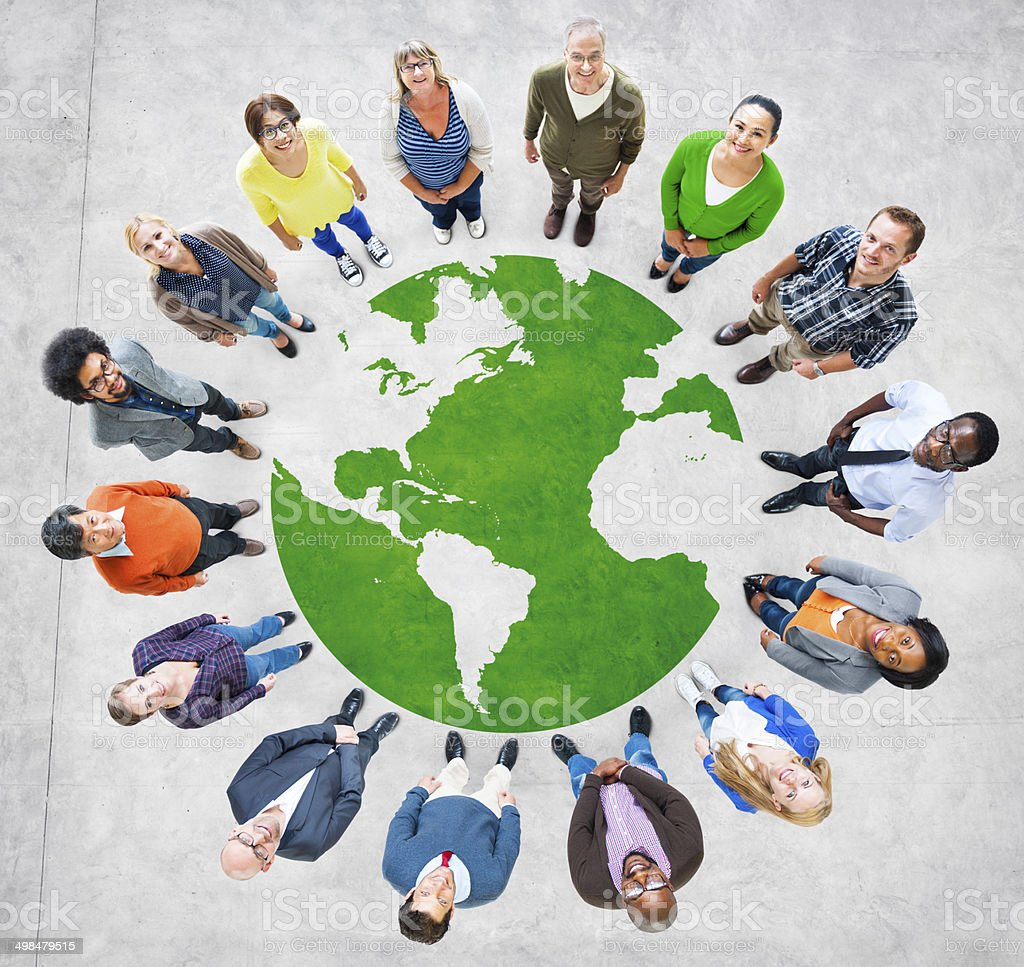 Diverse people stand around a global graphic People standing around an image of the globe.  A green and gray globe appears on the ground, and there is a multi-racial group of people standing around it. Aerial View Stock Photo