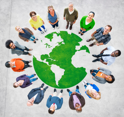 Diverse People Stand Around A Global Graphic Stock Photo - Download Image Now