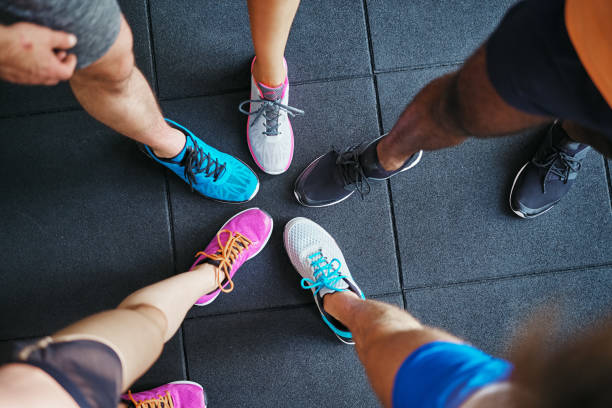Diverse people wearing running shoes standing in a gym stock photo