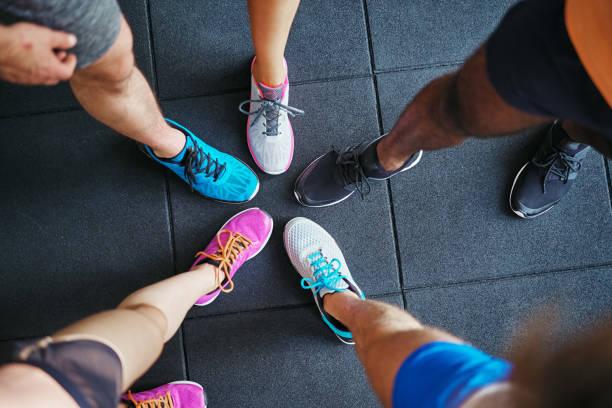 diverse menschen tragen laufschuhe stehen in einem fitnessstudio - joggingschuhe stock-fotos und bilder