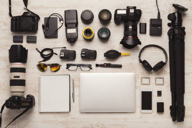 Diverse personal equipment for photographer Set of modern photographic equipment on white wooden table, top view. Professional tools of creative designer, photographer workplace background photographic equipment stock pictures, royalty-free photos & images