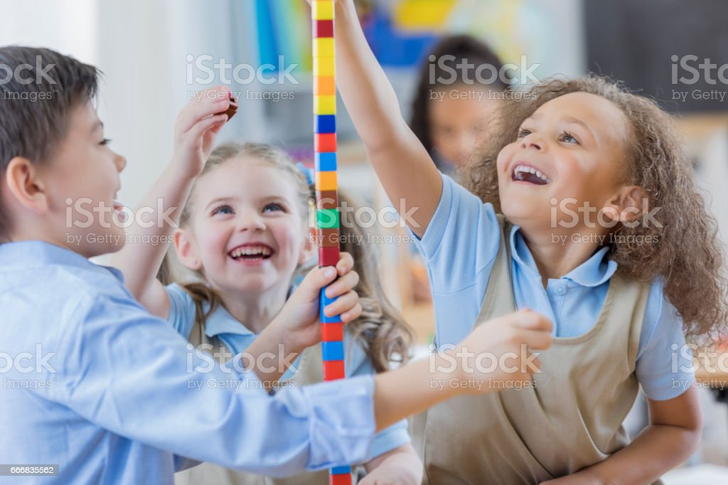 Diverse preschool friends play with counting cubes stock photo
