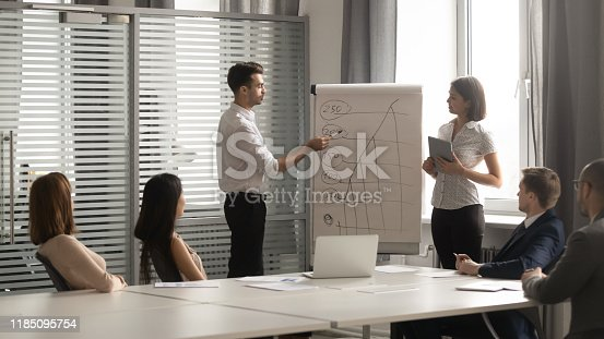 1031235468 istock photo Diverse professional business coaches give flip chart presentation in boardroom 1185095754