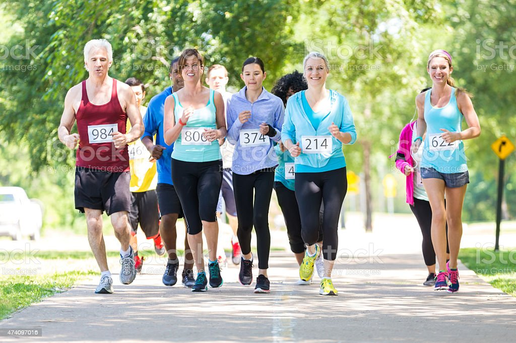 Diverse running team approaching finish line during marathon stock photo