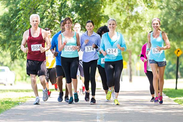 vielseitige running-team nähern ziellinie während marathon - laufveranstaltungen stock-fotos und bilder