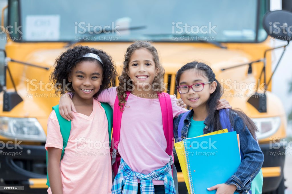 Diverse school friends in front of school bus stock photo
