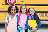 Happy diverse schoolgirl wait to get on school bus. They are smiling at the camera.