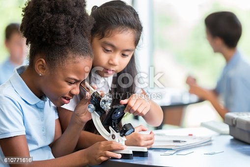 Focused African American and Asian schoolgirls help one another with their assignment in science class at a STEM elementary school. The African American girl is looking at something with a microscope.
