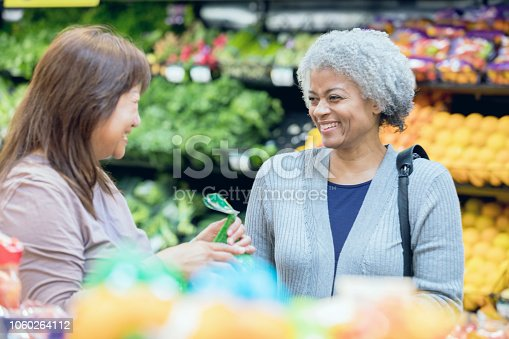 Senior adult African American woman is talking to senior adult Asian woman in a grocery store or supermarket. Active seniors are customers purchasing healthy food.