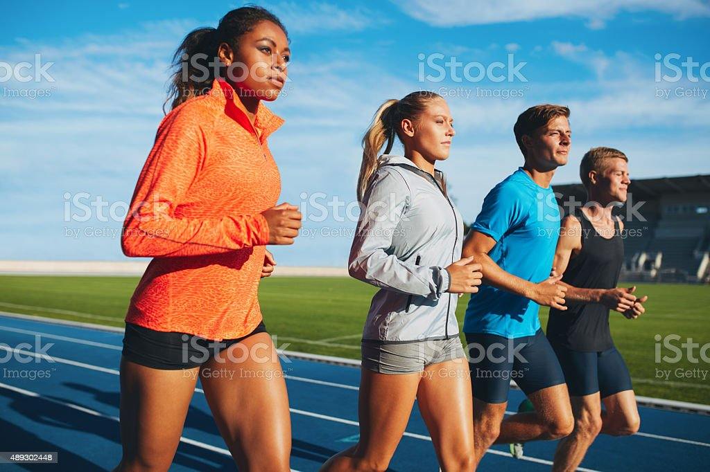 Diverse sports person running on racetrack stock photo