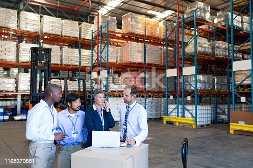 1165379503istockphoto Diverse staff discussing with each other in warehouse 1165370851