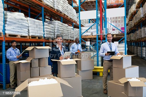 1165379503istockphoto Diverse staff looking at camera while working together in warehouse 1165372104