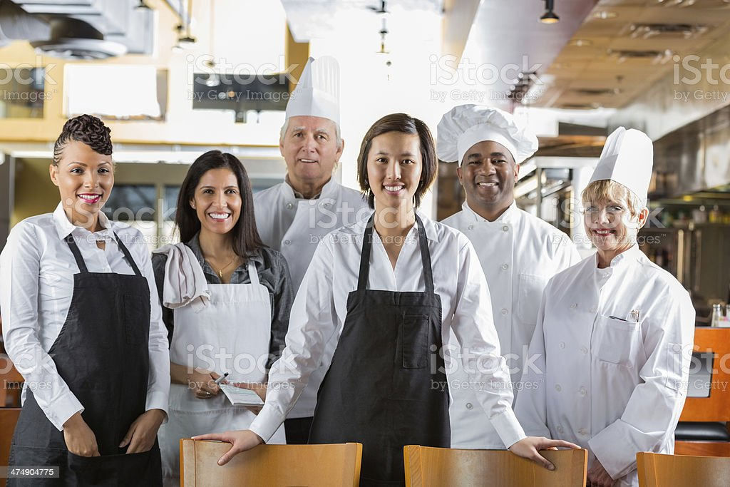 Diverse staff of chefs and waiters in modern restaurant kitchen royalty-free stock photo