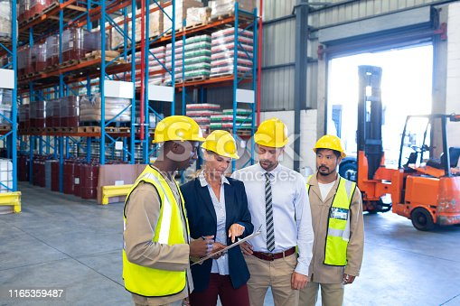 1165376915istockphoto Diverse staffs working together on clipboard in warehouse 1165359487