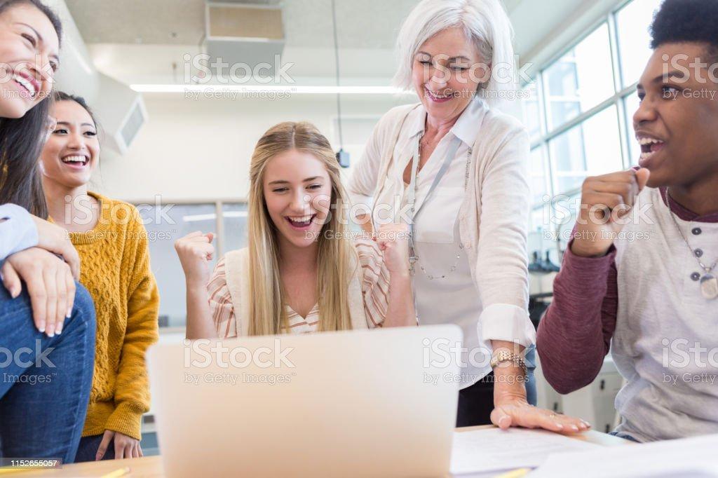 Cheerful diverse high school students show their science teacher a...