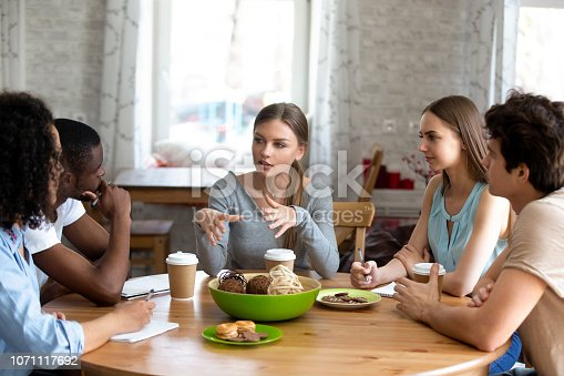Diverse multi-ethnic students sitting around circle table listen schoolmate ideas studying together in cafe. Multiracial best friends gathered together doing exercise homework making notes on notepad