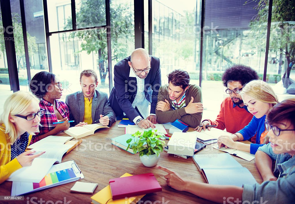 Diverse Students Studying with Their Professor stock photo