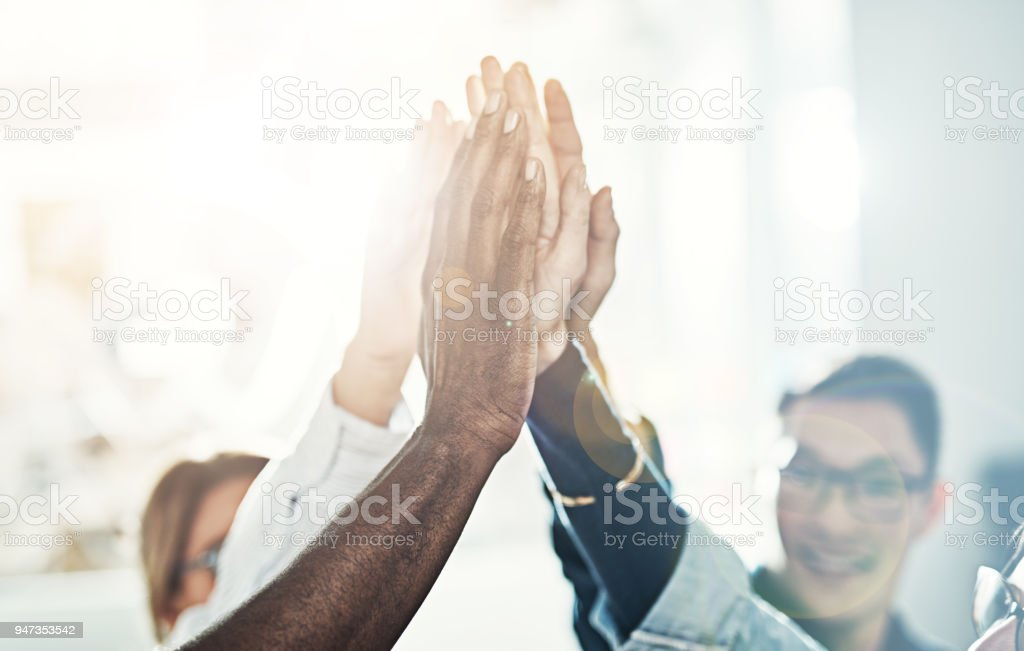 Diverse team of businesspeople high fiving together in an office stock photo