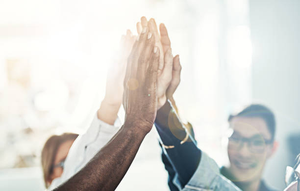 Diverse team of businesspeople high fiving together in an office Diverse team of work colleagues standing in a huddle together in a bright modern office high fiving each other dedicated stock pictures, royalty-free photos & images