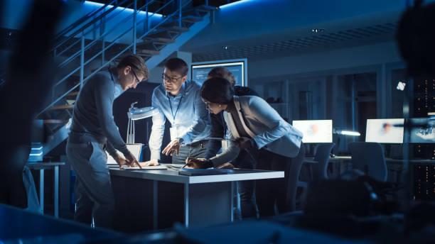diverso equipo de ingenieros de desarrollo electrónico de pie en el escritorio trabajando con documentos, resolviendo los problemas del proyecto tarde en la noche. especialistas que trabajan en diseño industrial ultra moderno. - ingeniero fotografías e imágenes de stock