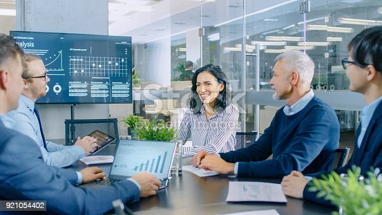 istock Diverse Team of Executives Have Meeting in a Conference Room. They Share Opinions, Statistics Show on Laptops and Tablets. In the Background TV Screen with Relevant Information about Company's Growth. 921054402