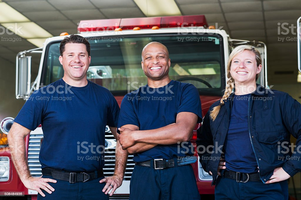 Diverse team of firefighters in front of fire engine stock photo
