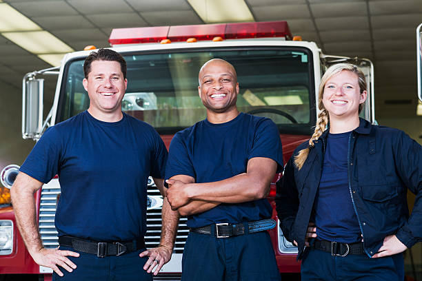 diverso equipo de bomberos en frente de camión de bomberos - bombero fotografías e imágenes de stock