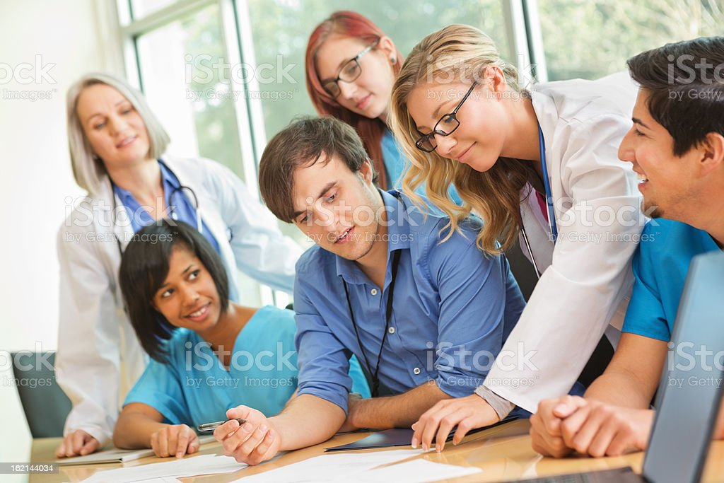 Diverse team of hospital employees consulting together doing medical research royalty-free stock photo