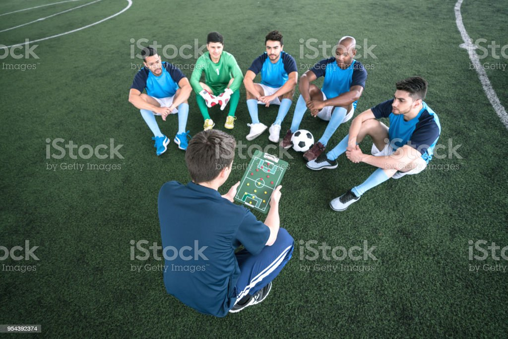 Male diverse team of indoor soccer paying close attention to his...