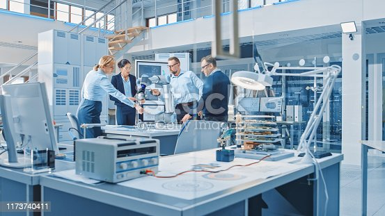 istock Diverse Team of Industrial Robotics Design Engineers Gathered Around Table with Modern Moving Robot Arm. Specialists Talking, Programming and Manipulating Robot Hand. Bright High Tech Facility 1173740411