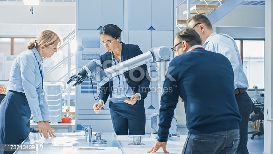 968289374istockphoto Diverse Team of Industrial Robotics Engineers Gathered Around Table With Robot Arm, They Manipulate and Program it to Pick Up and Move Metal Component. 1173740409