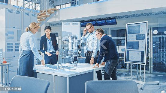 968289374istockphoto Diverse Team of Industrial Robotics Engineers Gathered Around Table With Robot Arm, They Manipulate and Program it to Pick Up and Move Metal Component. Bright Facility, Creative People 1173740415